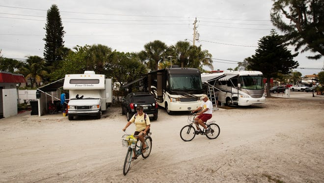 Lake Placid, Florida residents, Pat and Bob Kules head back to their camp site at the Red Coconut RV Park on Fort Myers Beach on Tuesday. The popular historic park might lose a portion of the property that parallels Estero Boulevard to an expansion project.