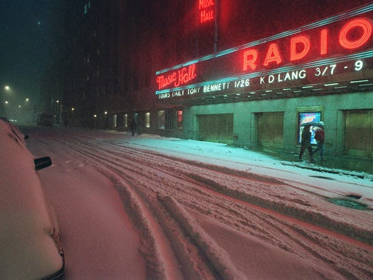 FILE - In this Jan. 7, 1996 file photo, people walk past Radio City Music Hall along a snow covered street in New York. A blizzard roared into the metropolitan area, dumping up to 2 inches of snow an hour that closed LaGuardia, Kennedy and Newark airports. (AP Photo/Wally Santana, File)
