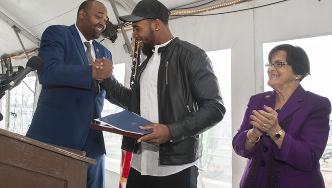Haason Reddick, a Camden native who played football at Haddon Heights High School and Temple University and is a potential NFL first-round draft pick, center, shakes hands with Assemblyman Arthur Barclay, next to Assemblywoman Patricia Egan Jones, right, during a ceremony to honor Reddick on the Battleship New Jersey on Monday.