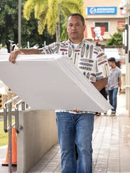 In this Sept. 13 file photo,  Mark Smith carries poster