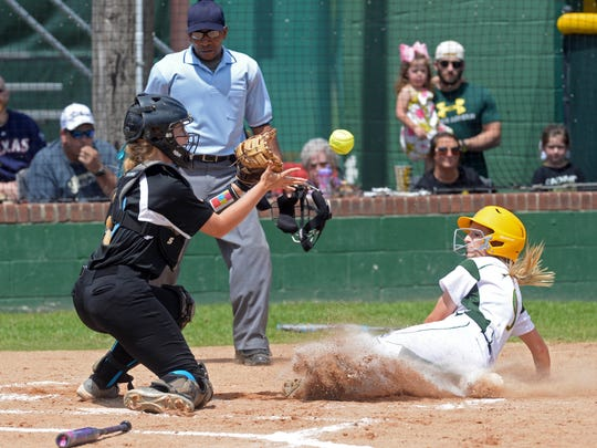 Shelby Brown slides into home plate beatng the throw