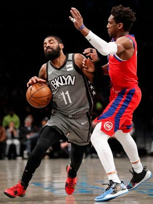 Pistons guard Langston Galloway, right, fouls Nets guard Kyrie Irving during the second half.
