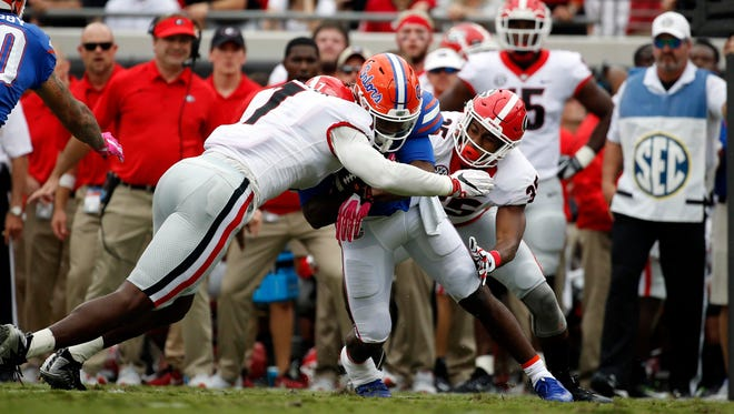 Georgia Bulldogs defensive back Aaron Davis (35) tackles Florida Gators running back Lamical Perine.