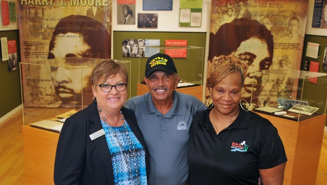 Committee member Melanie Glenn, of Seacoast Bank, Herman Cole, Colonel USAF, Ret. and Chairman of the Board of Directors at Parrish Medical Center, and Sonya Mallard, Moore Museum director of the Harry T. and Harriette V. Moore Memorial Park & Museum in Mims.