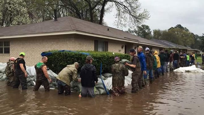 Volunteers surround the home of Gary Smith in Town and Country as they stack sandbags in an effort to stop the rising water from entering the house. The photo was taken by Dakota Duncan Smith. Her husband is Taylor Smith and the home belongs to his grandfather.