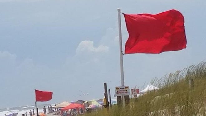 Red flags flying at Emerald Isle indicate dangerous surf conditions and advising against swimming in the ocean.