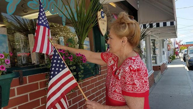 Janet Bennett, owner of the Gray Dolphin gift shop in Swansboro, decorates the shop for the Fourth of July holiday.