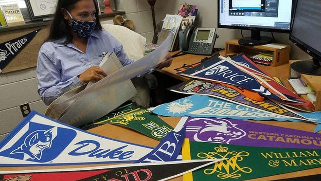Swansboro High School counselor Nicole Rains sorts through college banners used to be displayed around the school to show the variety of college and university options.