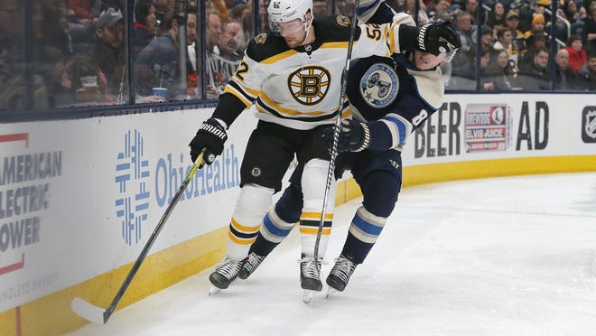 Boston Bruins center Sean Kuraly (52) takes control of the puck as Columbus Blue Jackets defenseman Zach Werenski (8) trails the play during the third period at Nationwide Arena on Jan. 14, 2020.
