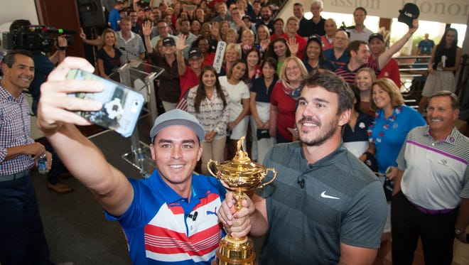 Rickie Fowler, left, takes a selfie of him and Brooks Koepka Tuesday at the PGA of America headquarters in Palm Beach Gardens, Fla. The two were delivering the Ryder Cup back to the PGA of America after the recent 17-11 win over the European team.