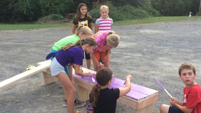Members of Girl Scout troop 40422 fix the benches in the soccer field at Cassavant School.