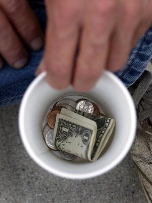 Panhandler Leo Knuckles shows his collection cup as he looks for some extra change along south Meridian Street downtown.