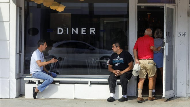 Dan Ponton, left, the owner of SurfSide Diner, and head chef Douglas Martinez, talk outside the diner on Friday before closing.
