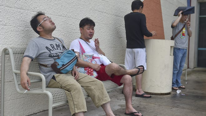 Shoppers take a smoke break in a designated smoking area outside Guam Premier Outlets in Tamuning on July 10.