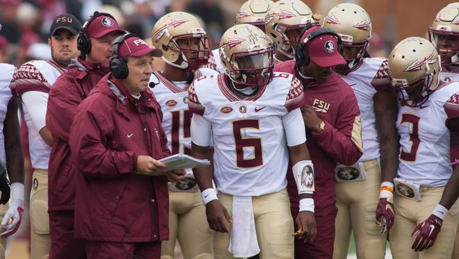 Florida State Seminoles quarterback Everett Golson (6) talks with head coach Jimbo Fisher in the huddle during a timeout in the first half against the Wake Forest Demon Deacons at BB&T Field.