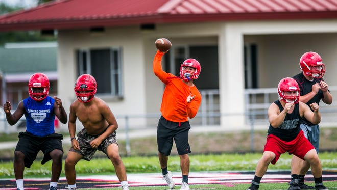Immokalee quarterback R.J. Rosales, center, runs through drills during the first spring practice at Immokalee High School on Monday, April 23, 2018.