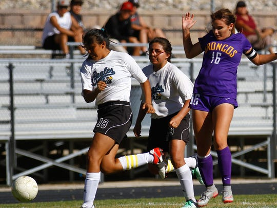 Navajo Prep's Kelly Charley, left, steals the ball from Kirtland Central's Christine Young on Sept. 8 at Eagle Stadium in Farmington.