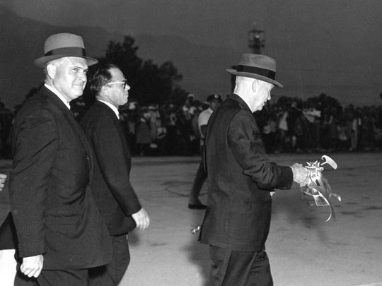 Pres. Eisenhower holding golf club at night.