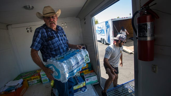 Four Corners Hope for Houston volunteer Dan Lee collects donated water Friday in the Sam's Club parking lot in Farmington.