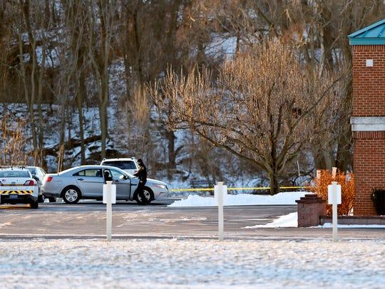 A law enforcement officer walks outside of Stillmeadow