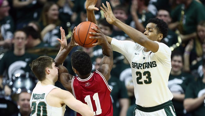 Indiana Hoosiers guard Yogi Ferrell (11) is defended by Michigan State Spartans guard Matt McQuaid (20) and Michigan State Spartans forward Deyonta Davis (23) during the second half of a game at Jack Breslin Student Events Center.