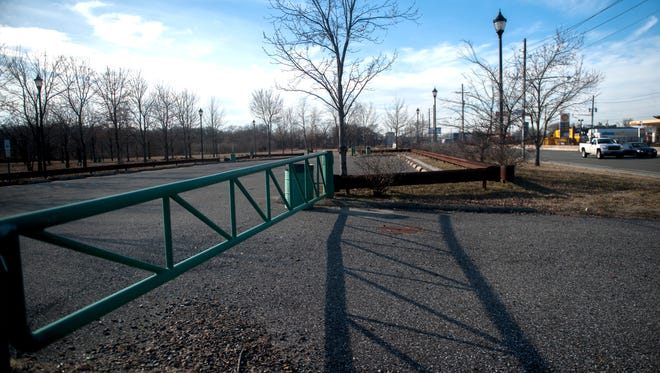 A gated parking lot sits next to the long-closed Gateway Park and the Admiral Wilson Boulevard in Camden .  03.01.16