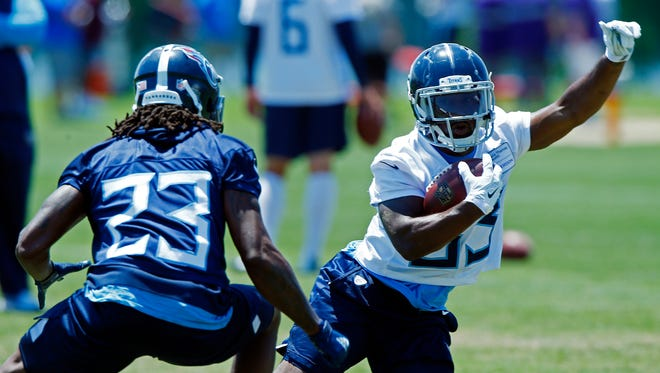 Titans running back Dion Lewis (33) avoids defensive back Tye Smith (23) during practice Tuesday.