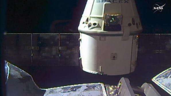 A SpaceX Dragon capsule separates from a robotic arm