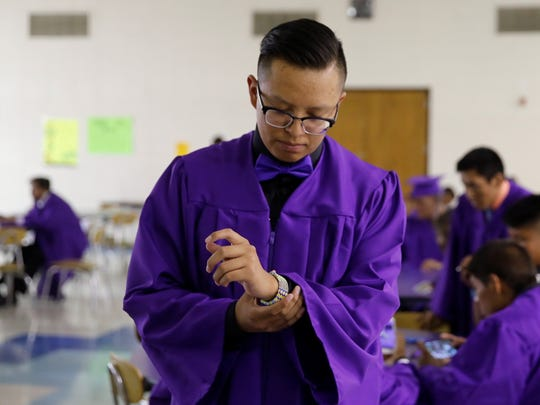 Kirtland Central High School senior Avin Jones adjusts his bracelet while waiting inside the school cafeteria on Friday in Kirtland before the beginning of the school's graduation ceremony.