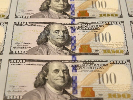 A sheet of uncut $100 bills makes its way through the printing process at the Bureau of Engraving and Printing Western Currency Facility on Sept. 24 in Fort Worth.  The federal printing facility is producing the colorful bills to include new security features.