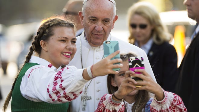 Pope Francis takes a photo with children whose parents work at the Lithuanian Embassy, outside the Apostolic Nunciature to the United States on Sept. 23, in Washington.