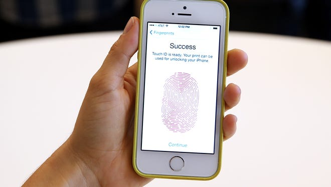 The new iPhone 5S with fingerprint technology is displayed during an Apple product announcement at the Apple campus in Cupertino, California.