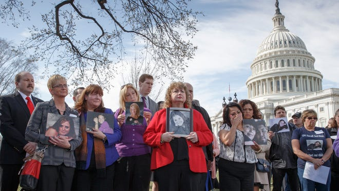 Families of victims of a General Motors safety defects in small cars hold photos of their loved ones as they gather on the lawn on Capitol Hill in Washington. Families of those who died in General Motors cars with defective ignition switches want prosecutors to go after GM insiders responsible for letting the problems fester for more than decade, and perhaps for covering them up.