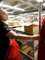 Employee Brook Goodwin unpacks, sorts and prices Wisconsin Badgers Final Four T-shirts on Monday at Scheels in Grand Chute.
