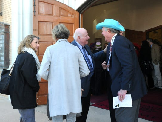 People visit after a funeral service for Roy Helen