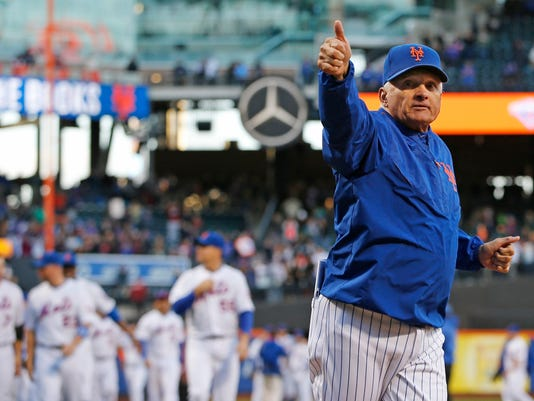 New York Mets manager Terry Collins, right, gives a thumbs up as he heads to the dugout after taking a walk around the field to thank fans after the Mets 1-0 defeat of the Washington Nationals in their final regular season baseball game in New York, Sunday, Oct. 4, 2015. (AP Photo/Kathy Willens)