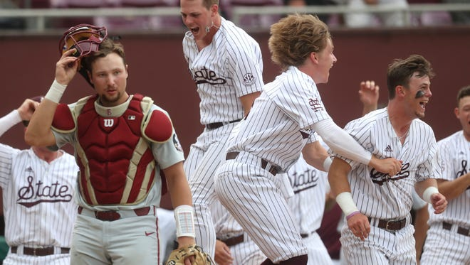 Mississippi State players celebrate their walk-off 3-run home run by Elijah MacNamee to defeat the Seminoles 3-2 as Florida State's Cal Raleigh walks off the field in their NCAA Regional elimination game at Dick Howser Stadium in Tallahassee, Fla. on Saturday, June 2, 2018. (Joe Rondone/Tallahassee Democrat via AP)
