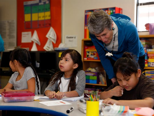 U.S. Secretary of the Interior Sally Jewell talks with first-grade students, from left, Mikayla Jim, Sophia White and Shaundeena Foster, on Thursday at Cove Day School in Cove, Ariz.
