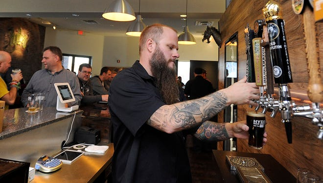 Chad Petit pours a beer during the Hydra Beer Company taproom grand opening in Sioux Falls, S.D., Friday, Dec. 18, 2015.