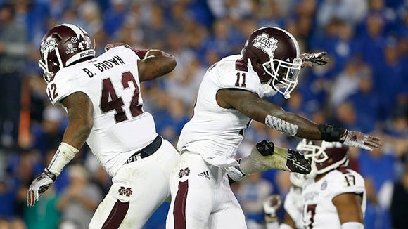 Oct 25, 2014; Lexington, KY, USA; Mississippi State Bulldogs linebacker Beniquez Brown (42) and defensive back Kivon Coman (11) celebrate during the game against the Kentucky Wildcats in the second half at Commonwealth Stadium. Mississippi State defeated Kentucky 45-31. Mandatory Credit: Mark Zerof-USA TODAY Sports