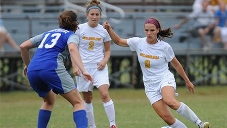 Samantha Beck (left) stands behind midfielder Christine Clark as she takes the ball downfield. Beck had two goals and an assist for the Sea Gulls Monday.