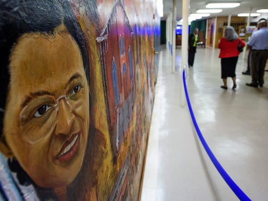 Rosa Parks face is seen as tourists look at the mural