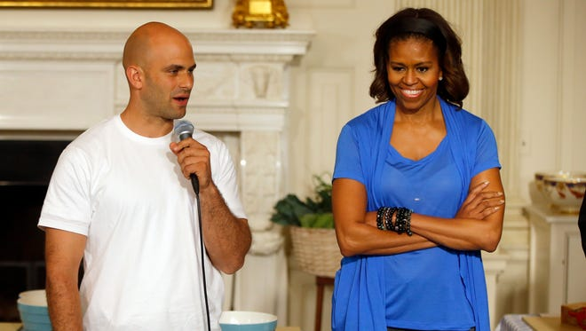 """First lady Michelle Obama stands with Sam Kass, White House Senior Policy Adviser for Nutrition Policy, before they make salads from vegetables harvested from the White House garden with area students in the State Dining Room of the White House in Washington on June 12, 2104. President Barack Obama's personal chef is leaving after nearly six years in which, unlike any assistant White House chef before him, he cooked up policy alongside his meals. Kass held the title of senior policy adviser for nutrition policy, which gave him a seat at the table to help administration officials hash out everything from an updated """"Nutrition Facts"""" label for processed foods to new government standards to cut the amount of fat, calories and sodium in federally subsidized school meals."""