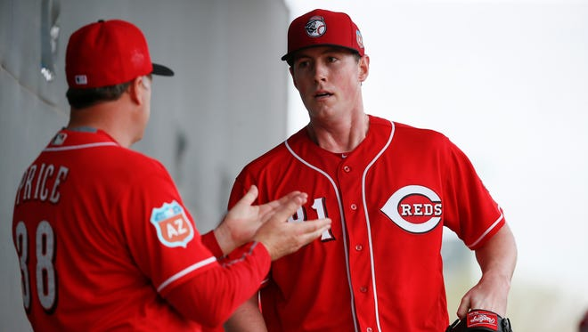 Cincinnati Reds manager Bryan Price (38), left, talks to pitcher Tim Melville (81) during Cincinnati Reds spring training, Thursday, Feb. 18, 2016, in Goodyear, Arizona.