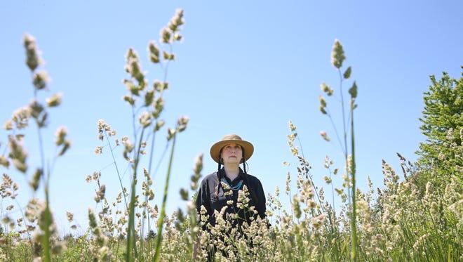 Christina Kretchmer walks along trails she has mowed around her 20-acre farm home in Henrietta Wednesday, June 1, 2016.