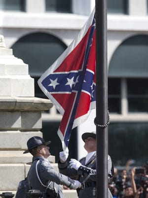 An honor guard from the South Carolina Highway patrol removes the Confederate battle flag from the Capitol grounds in Columbia, S.C., ending its 54-year presence there, on Friday, July 10, 2015.