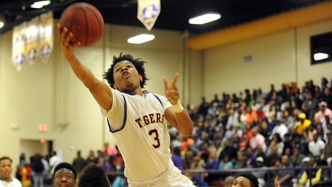 Hattiesburg's Michael Woodard (3) drives to the basket against Oak Grove in the Class 6A second-round playoff game at Watkins Gym.
