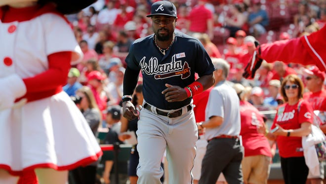Atlanta Braves second baseman Brandon Phillips (4) runs back the dugout after greeting a fan before the National League baseball game between the Atlanta Braves and the Cincinnati Reds, Saturday, June 3, 2017, at Great American Ball Park in Cincinnati.