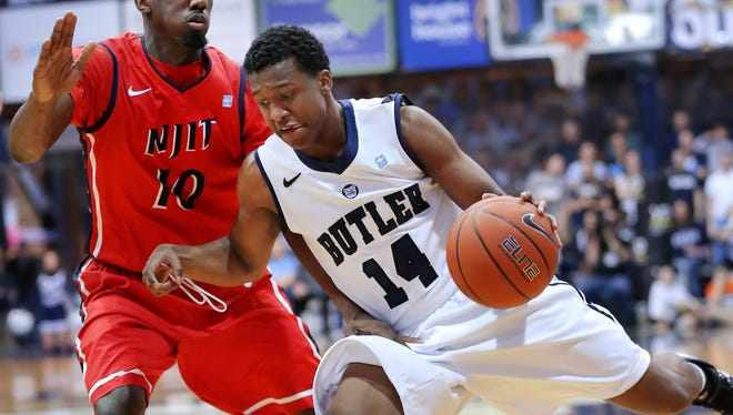Butler's Rene Castro lunges into NJIT's Daquan Holiday in the first half of their game held at Butler University on Saturday, Decmber 28, 2013.  Butler beat NJIT 66-48.