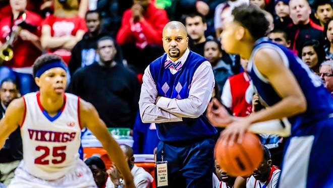 Everett Boys Basketball Head Coach Desmond Ferguson ,center, watches Leandre Wright, 25, of Everett defend a Saginaw Arthur Hill player during their Class A state semifinal game  Friday.